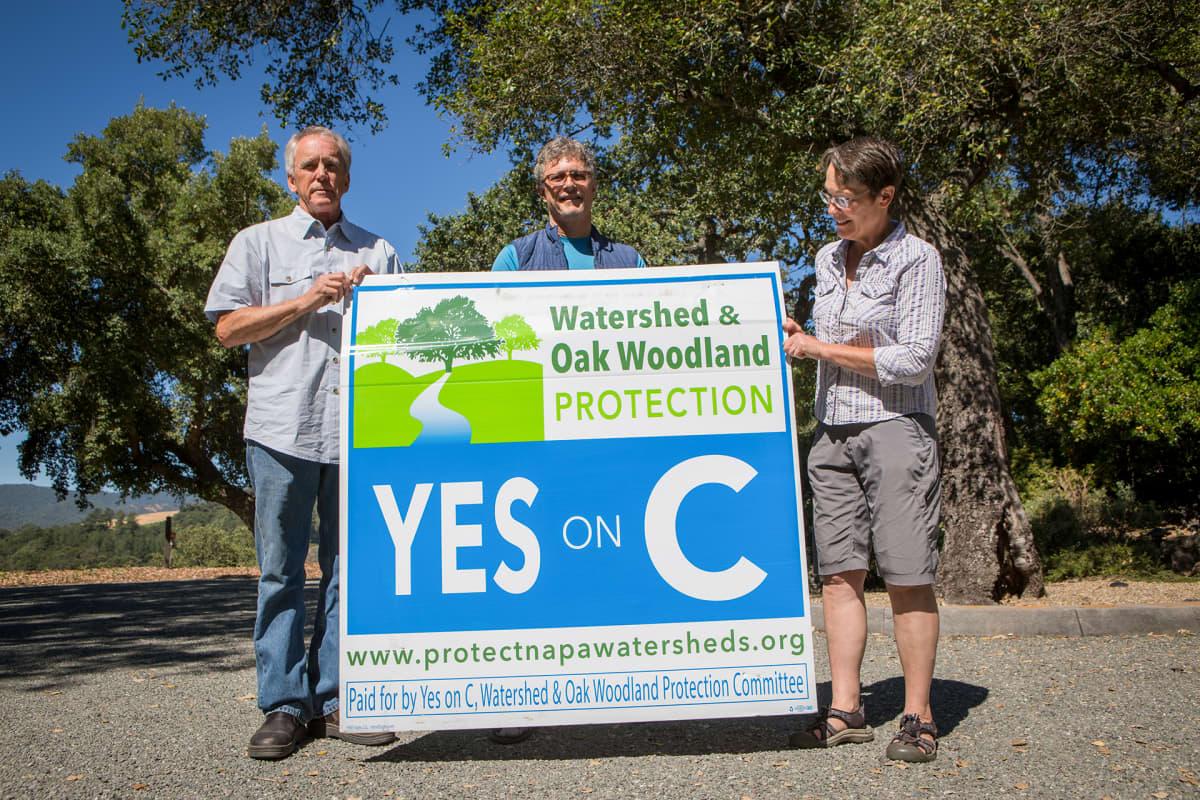 Yes on C-kyltti, jota pitävät Mike Hackett, Jim Wilson ja Chris Benz.