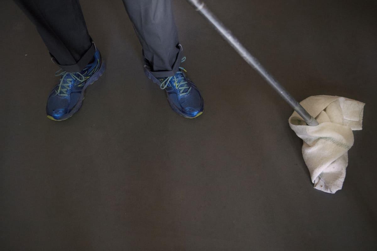 Siivooja moppaa lattiaa.