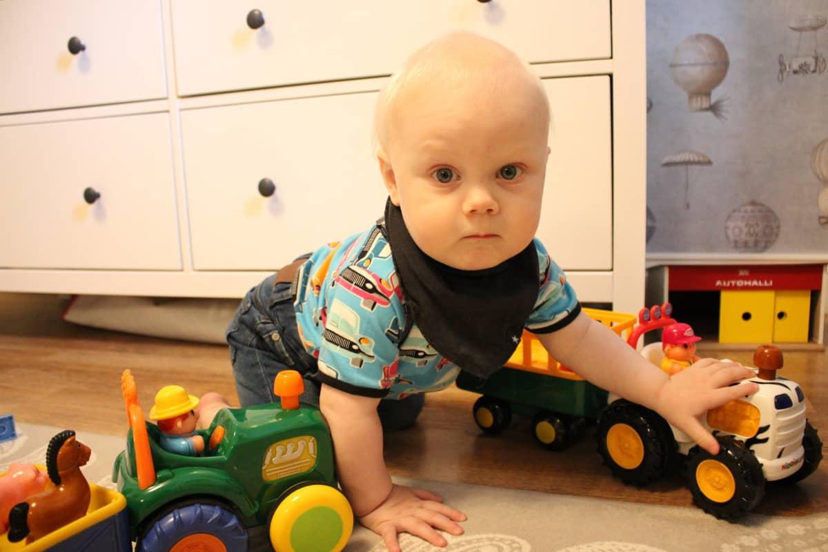 Vuoden ikäinen lapsi leikkii leluilla.