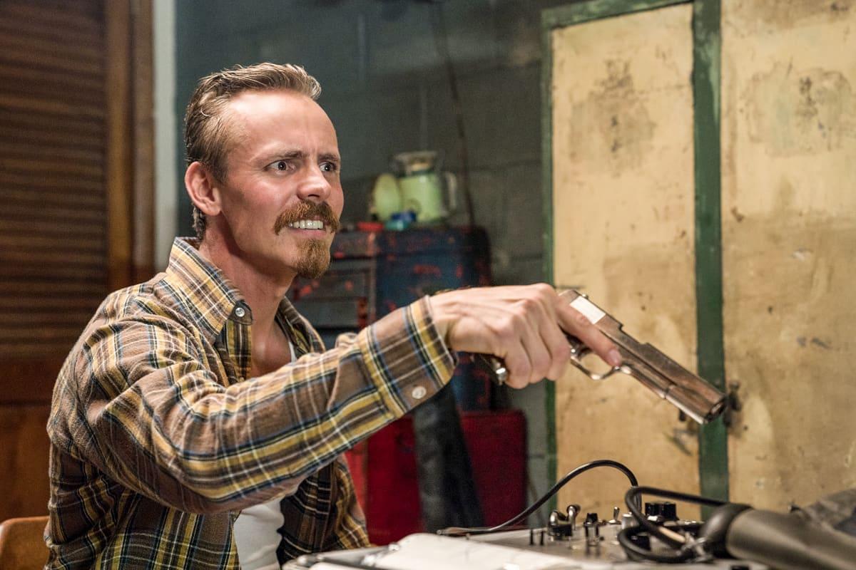 mies pistooli kädessään