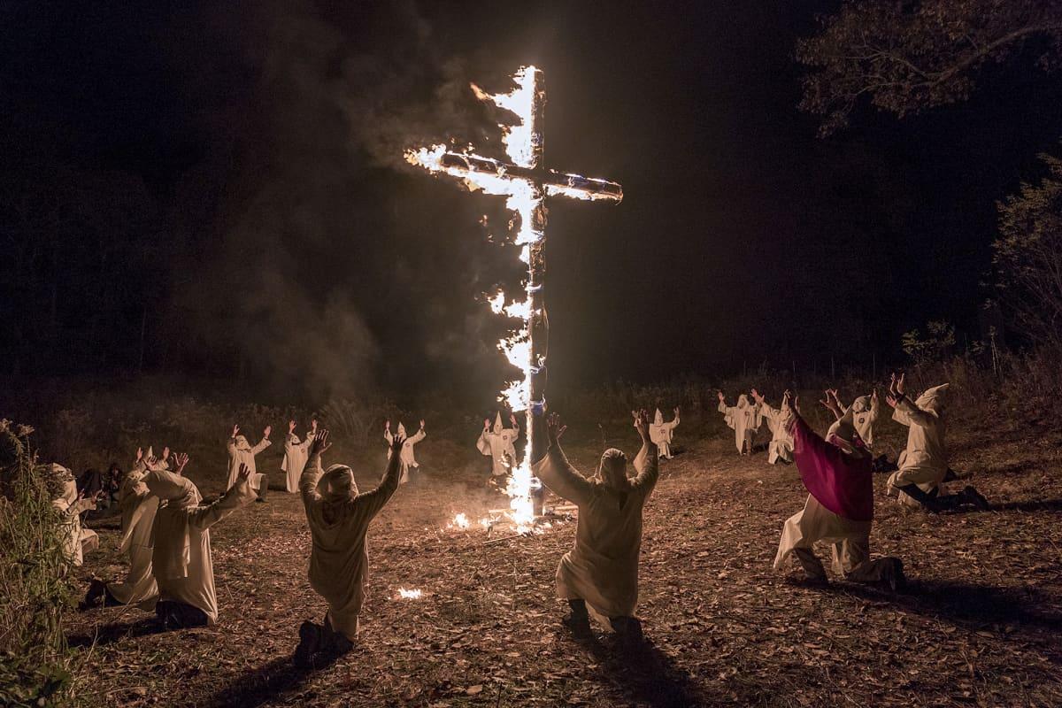 palava risti ja huppupäisiä miehiä