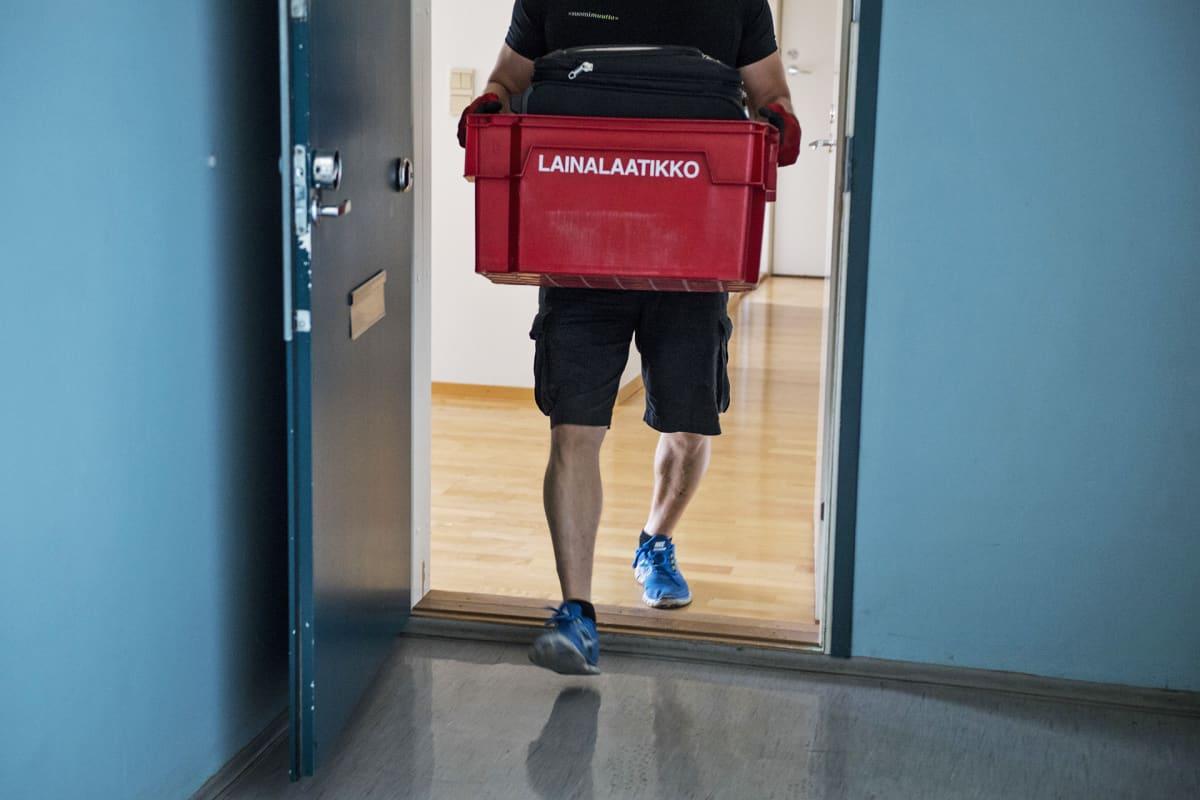 Muuttomies kantaa muuttolaatikkoa.