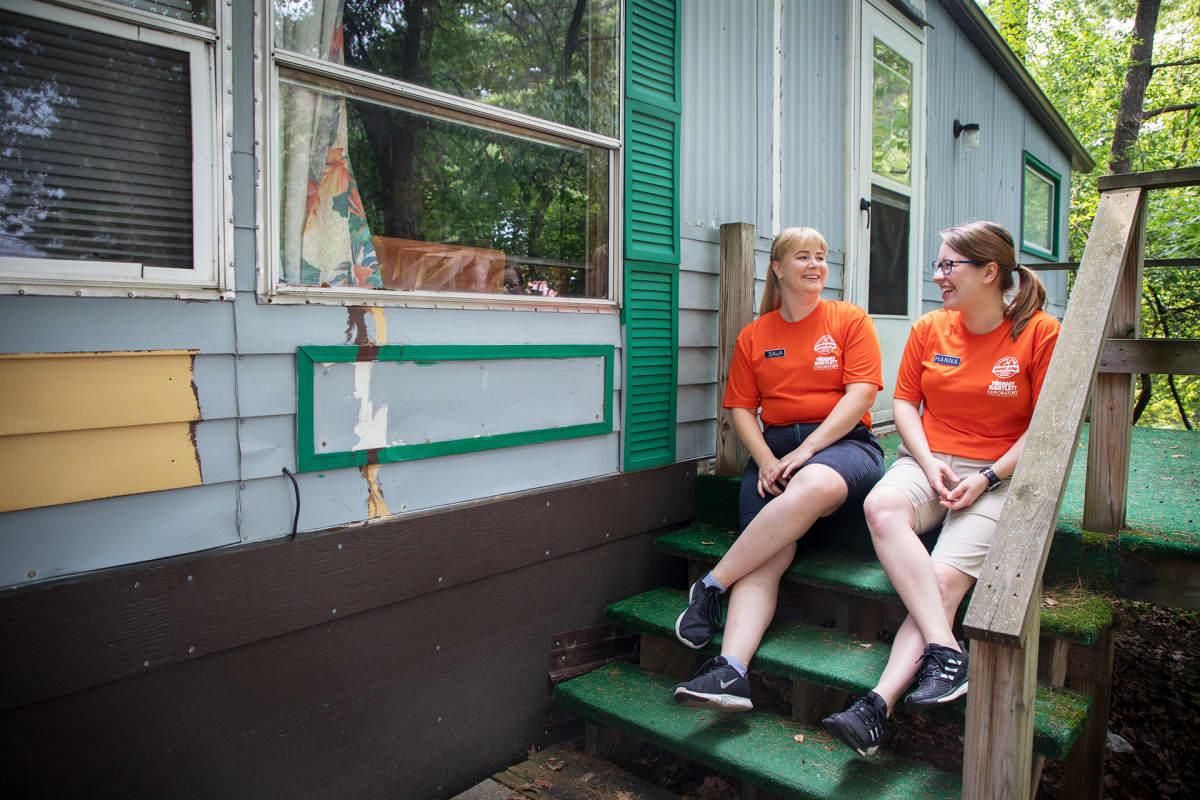 Suomalaiset kesätyöntekijät istuvat talon portailla.