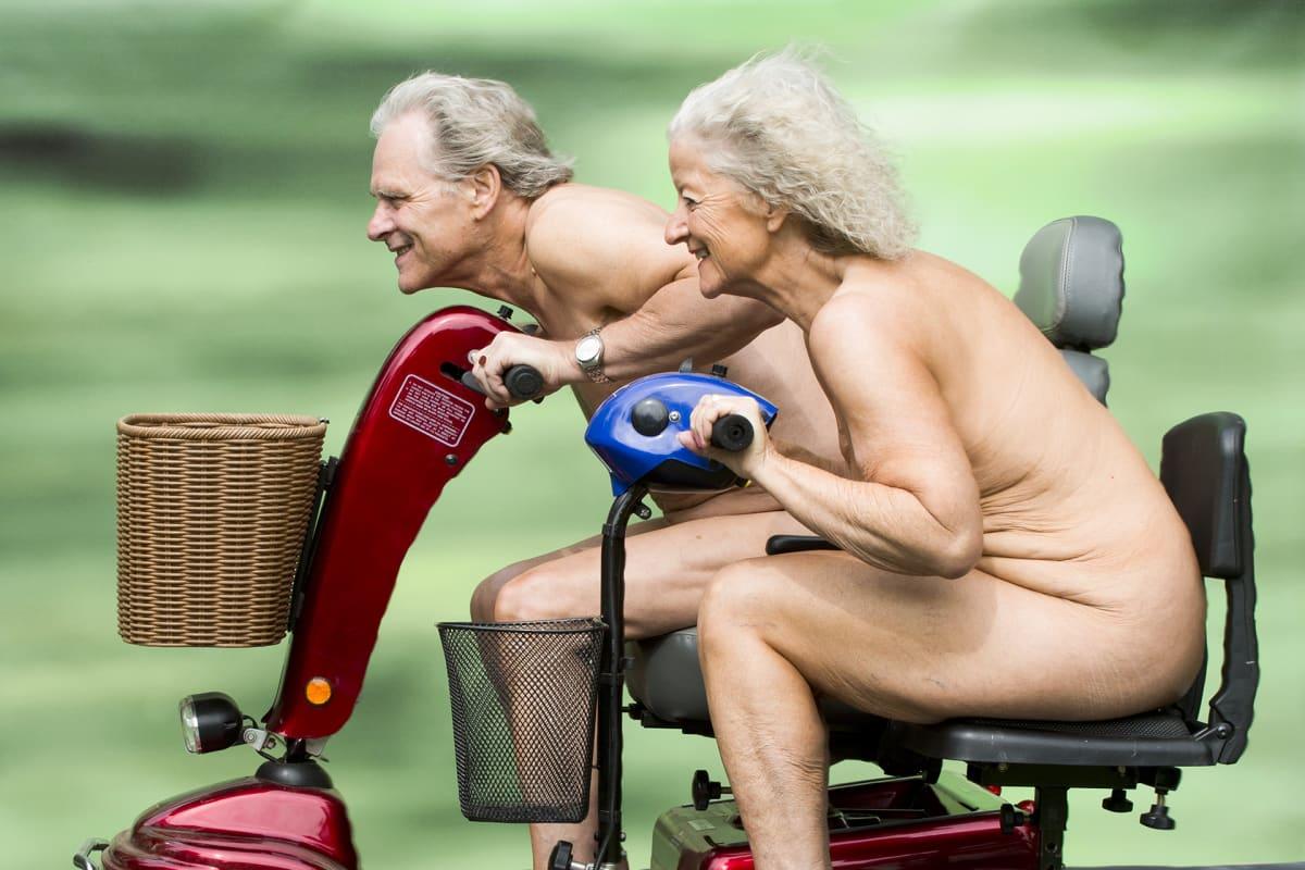 Vanha mies ja nainen ajavat kolmipyöräisillä mopoilla alasti.