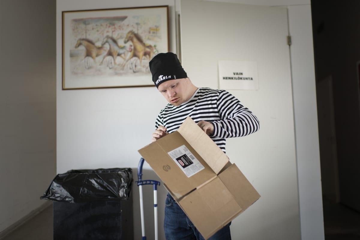 Samuli Kivinen taittelee pahvilaatikoita.