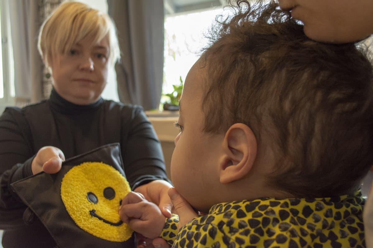 Aino Odedeyi esittelee koskettelukirjaa Olavi-pojalleen.