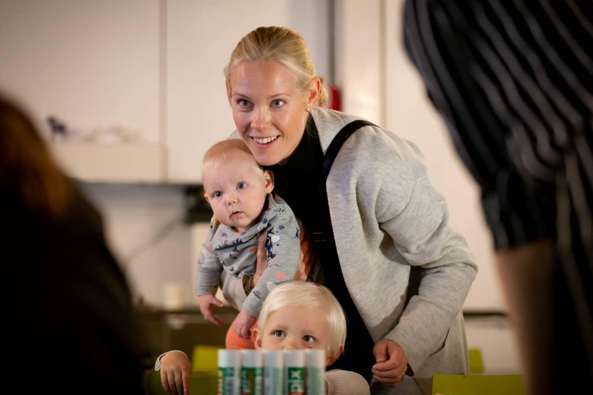 Seitsenkuinen Ilona-vauva seuraa tarkasti tapahtumia äitinsä Kukka-Maaria Sysimetsän sylistä. Kaksivuotias Eemeli pärjää jo melkein omillaan.