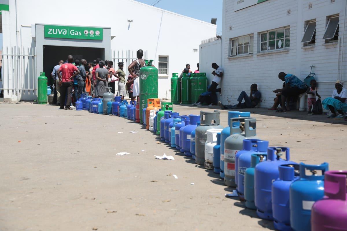 Kaasupulloja jonossa ja ihmisiä jonottamassa huoltoasemalle.