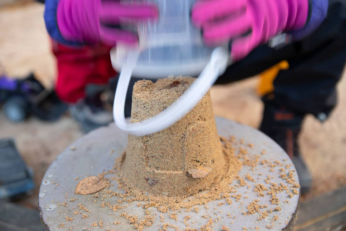 Lapsi tekee hiekkakakun ämpärillä.