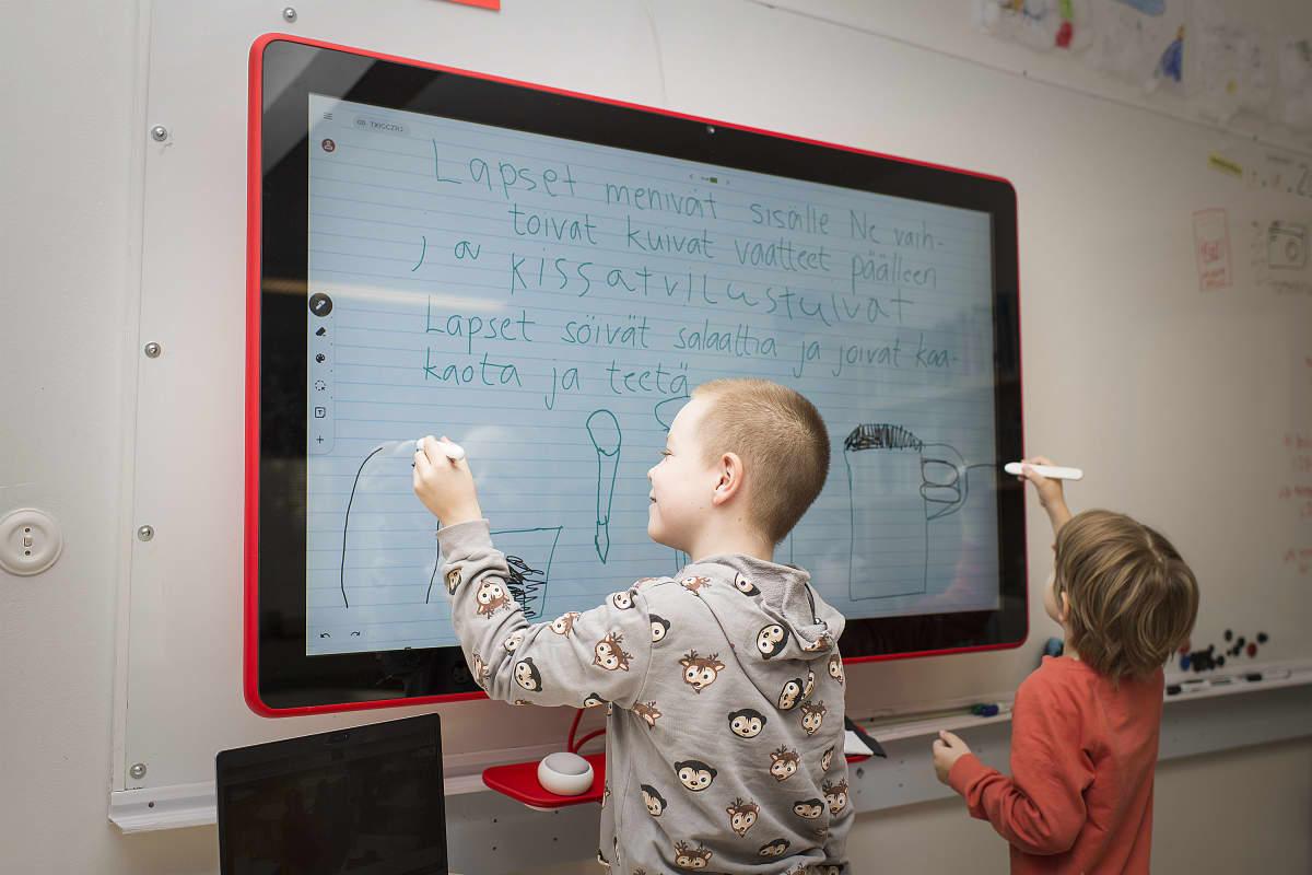 Oppilaita kirjoittamassa Jamboardille.