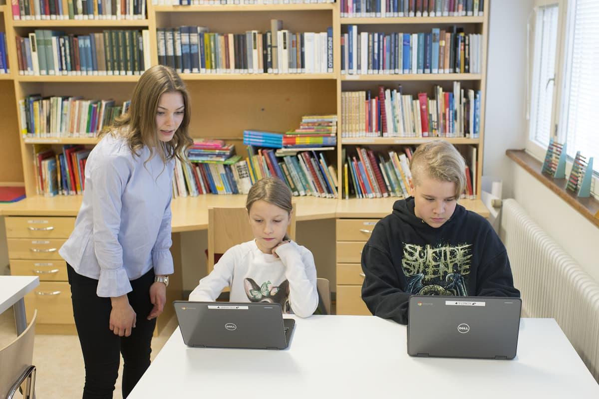 Opettaja Tiina Kuusiluoma opastaa Pauanne Kannussaarta ja Konsta Kumpulaista.