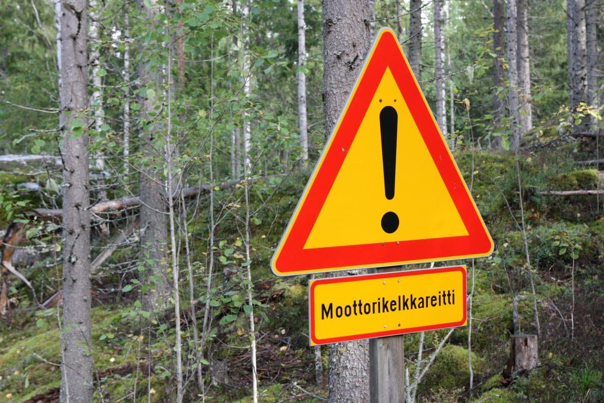 Moottorikelkkareitin liikennemerkki metsän reunassa.