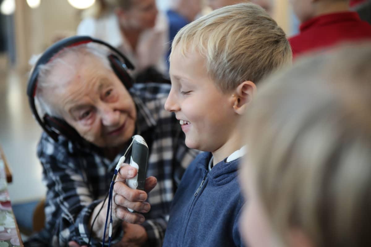 101-vuotias Lydia Haaksalo kommunikoi kakkosluokkalaisen Aatoksen kanssa apulaitteen välityksellä.