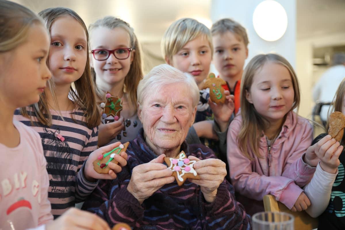 88-vuotias Martta Kuuva ja iltapäiväkerhon lapset koristelivat yhdessä pipareita.