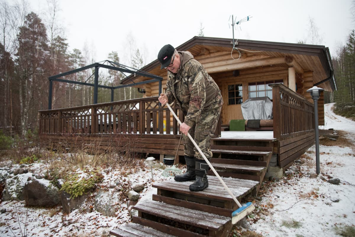 Pekka Hujanen lakaisee mökin portaita.