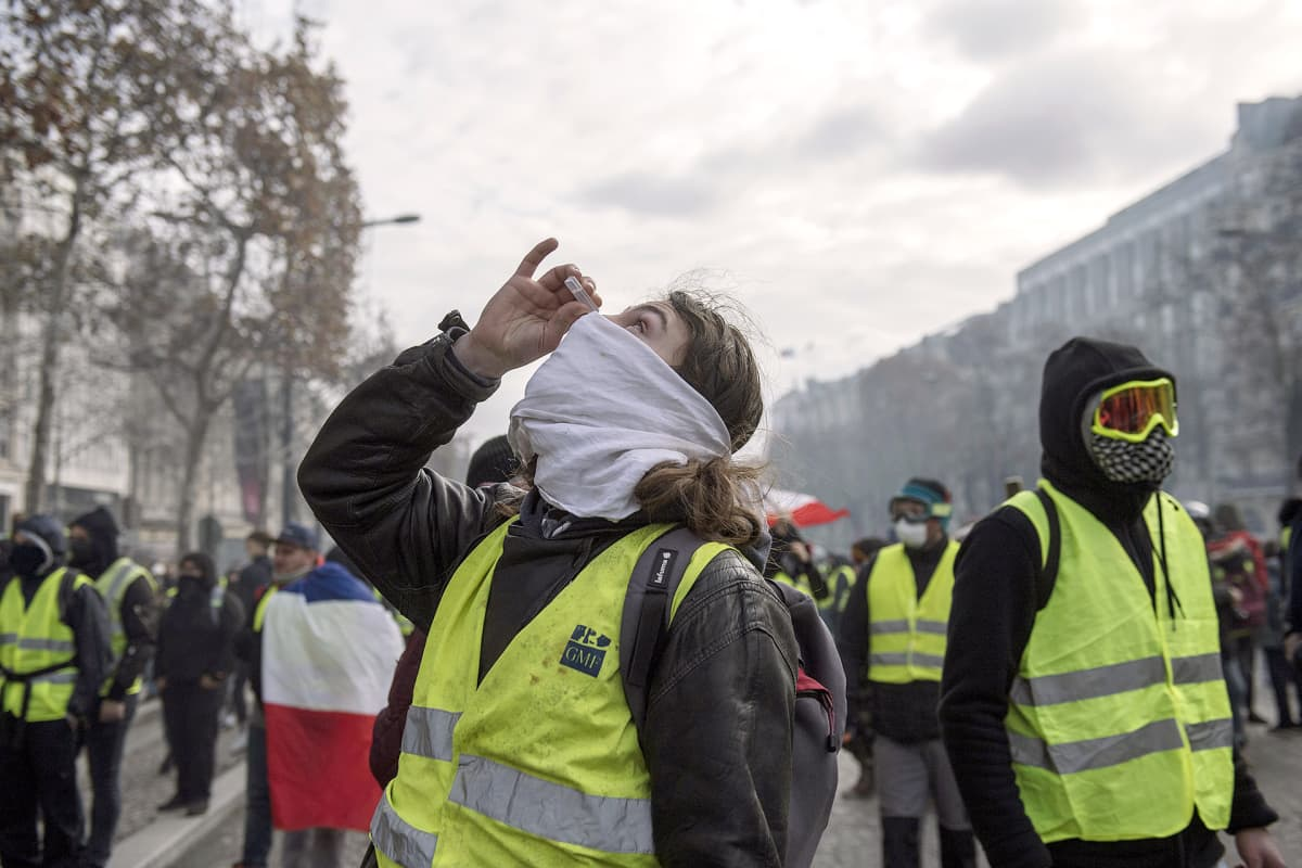 Keltaliivi-mielenosoittaja puhdistaa silmiään silmätipoilla Pariisissa 8. joulukuuta.