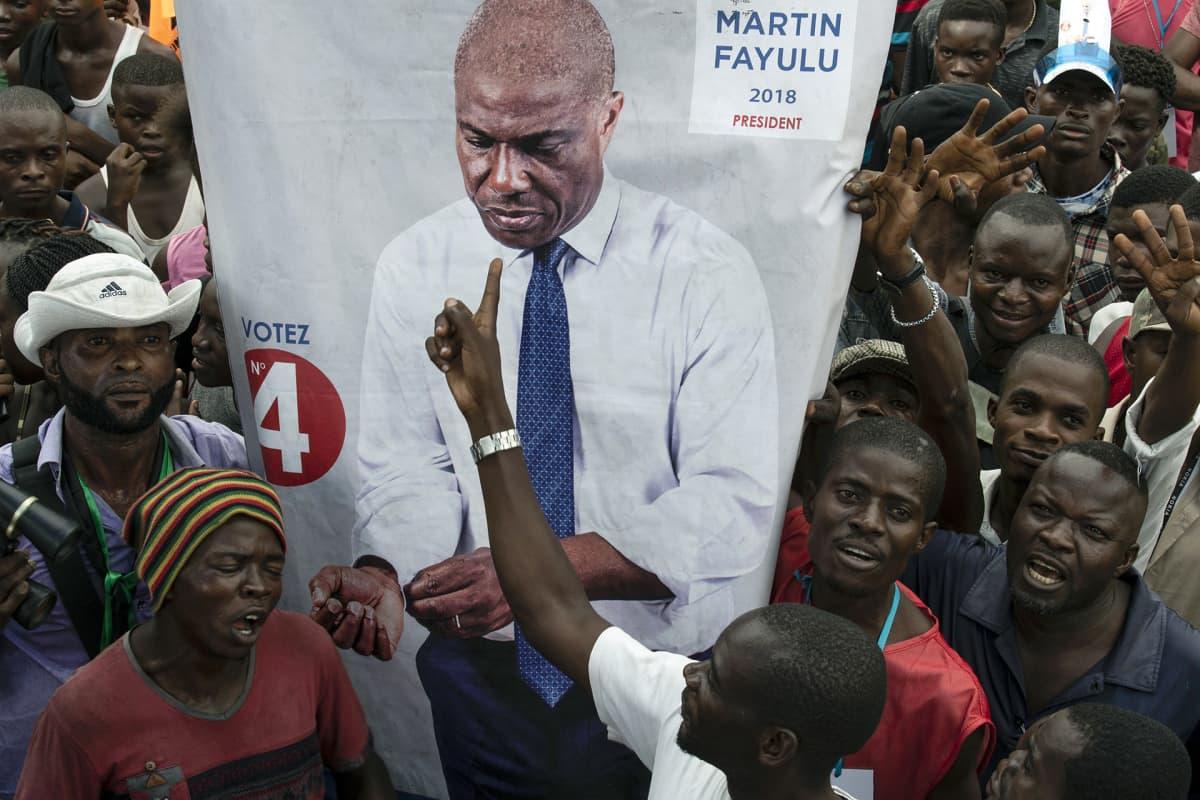 Martin Fayulun kannattajat kantavat Martin Fayulun kuvabanderolia.