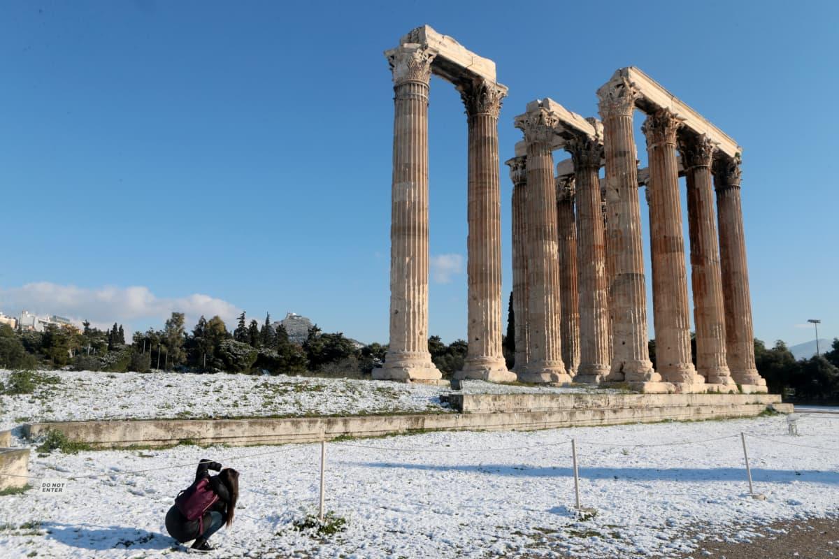 Nainen kuvaa Olympoksen Zeuksen temppeliä Ateenassa.