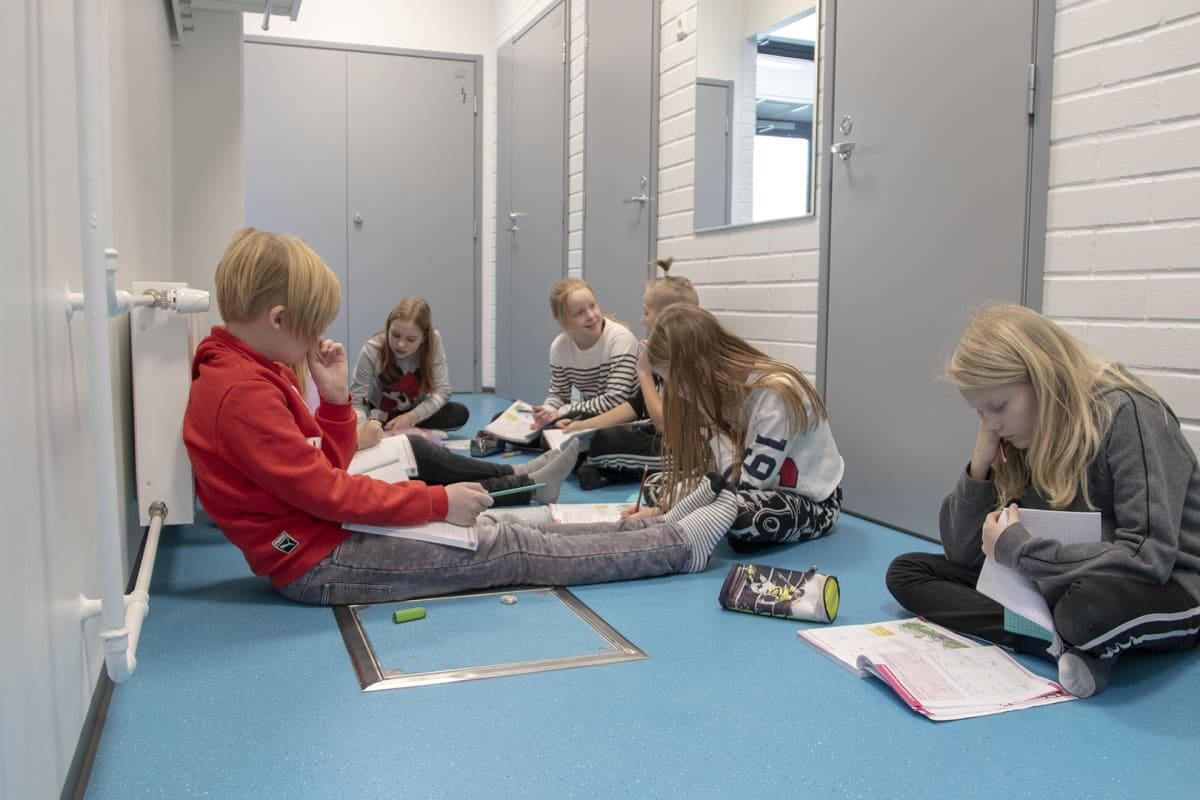 Oppilaita käytävällä istumassa Tyrnävän Rantaroustin koululla