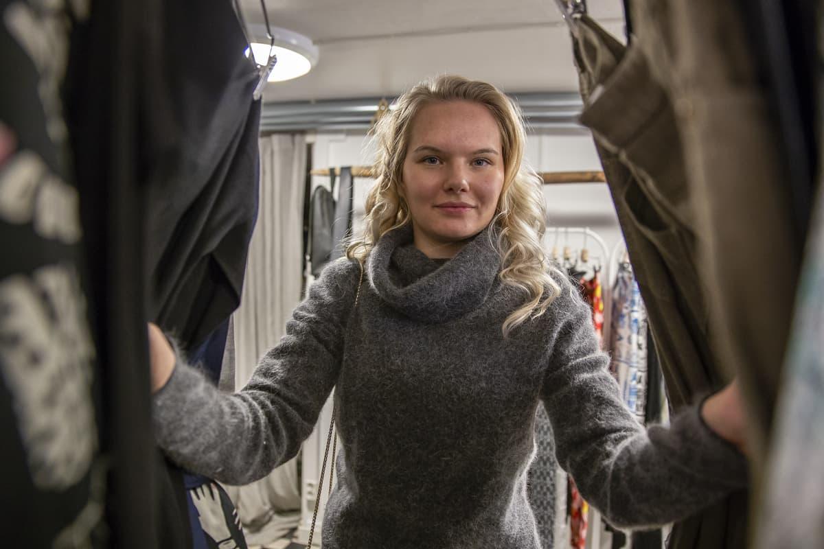 Nainen katsoo kameraan vaaterekissä olevien vaatteiden takaa.