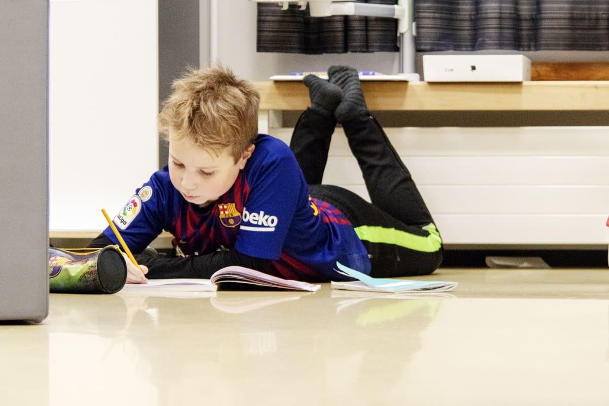 Oppilas tekee koulutehtäviä lattialla maaten.