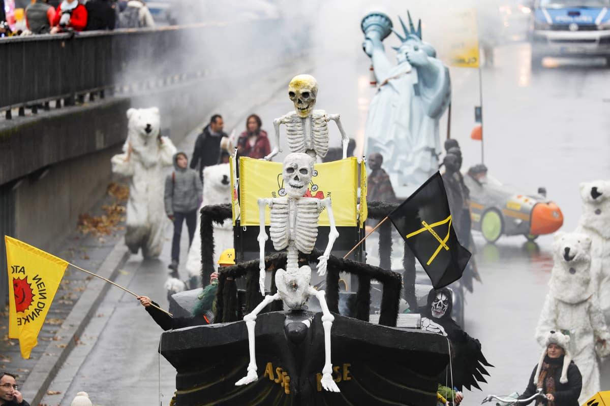 """Mielenosoitus ilmaston puolesta. Kuorma-auton lavalle rakennettu """"nooan arkki"""" jonka kyydissä kaksi luuranko. Taaempana näkyy miniatyyri vapaudenpatsas ja kolme kävelevää jääkarhua."""