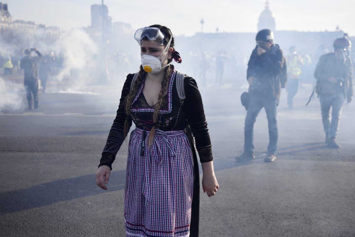 Hengitysmaskiin pukeutunut nainen keltaliivien mielensoituksessa Pariisissa.