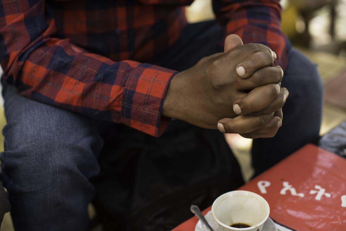 Miehen kädet ja kahvikuppi.