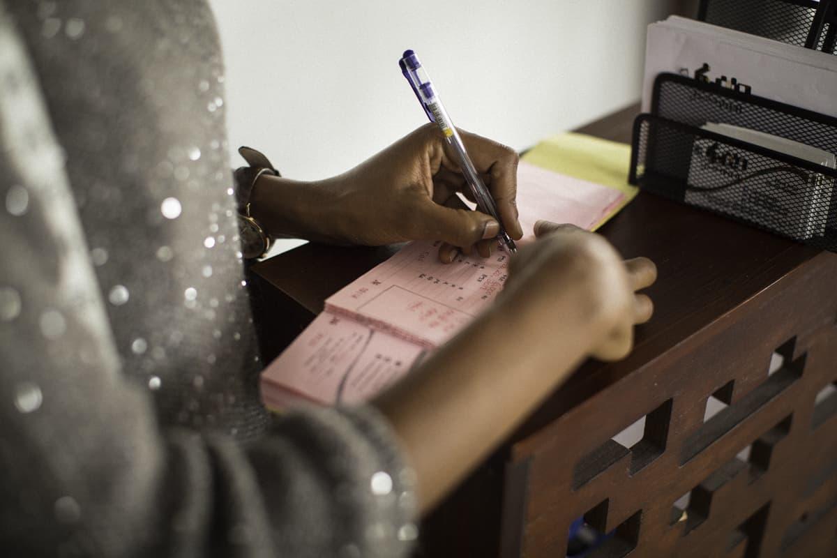 Naisen kädet kirjoittavat kuittia.