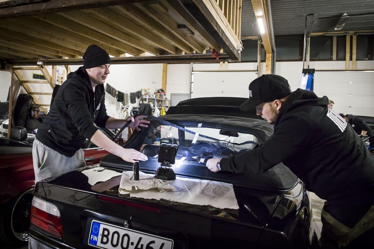Miehet korjaavat autoa.