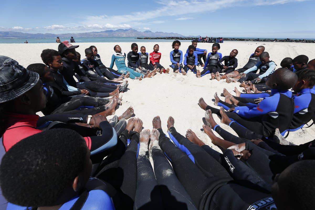 Etelä-afrikkalaisset lapset meditoivat rannalla.