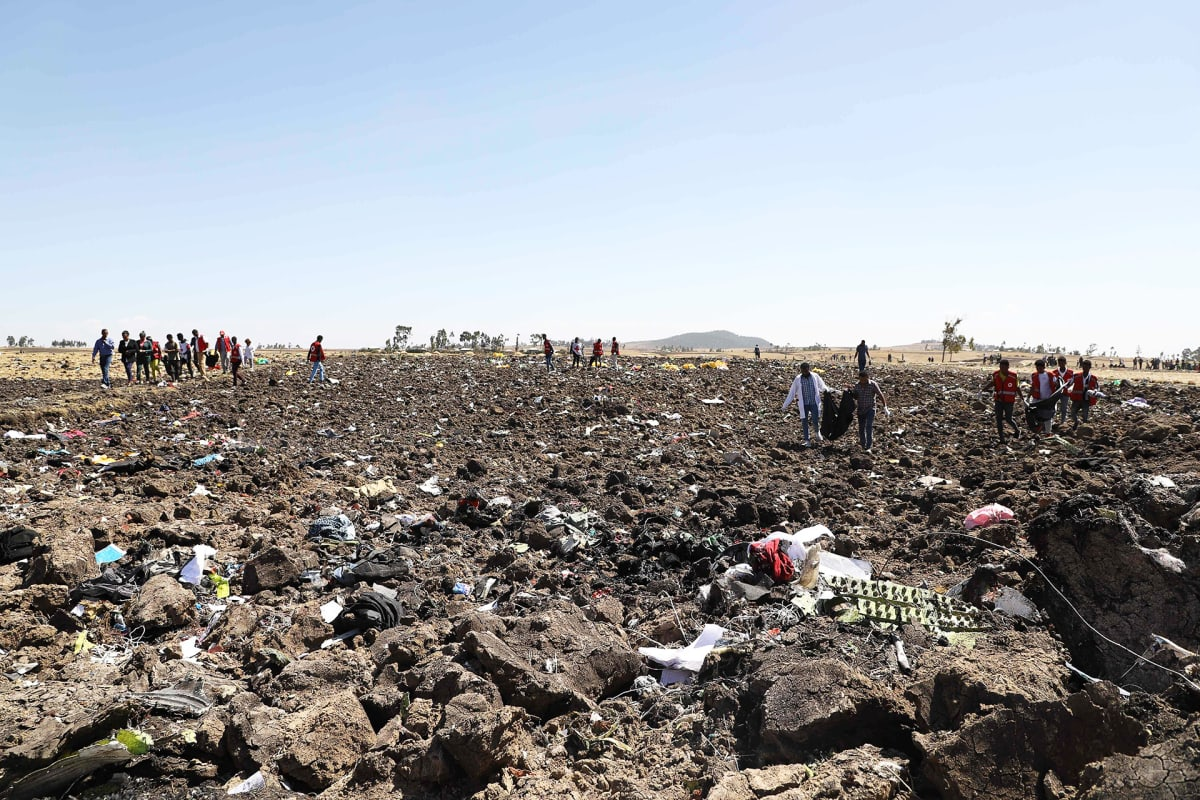 Pelastusmiehistöt keräävät matkustajien ruumiita ja tavaroita onnettomuuspaikalla Etiopiassa.