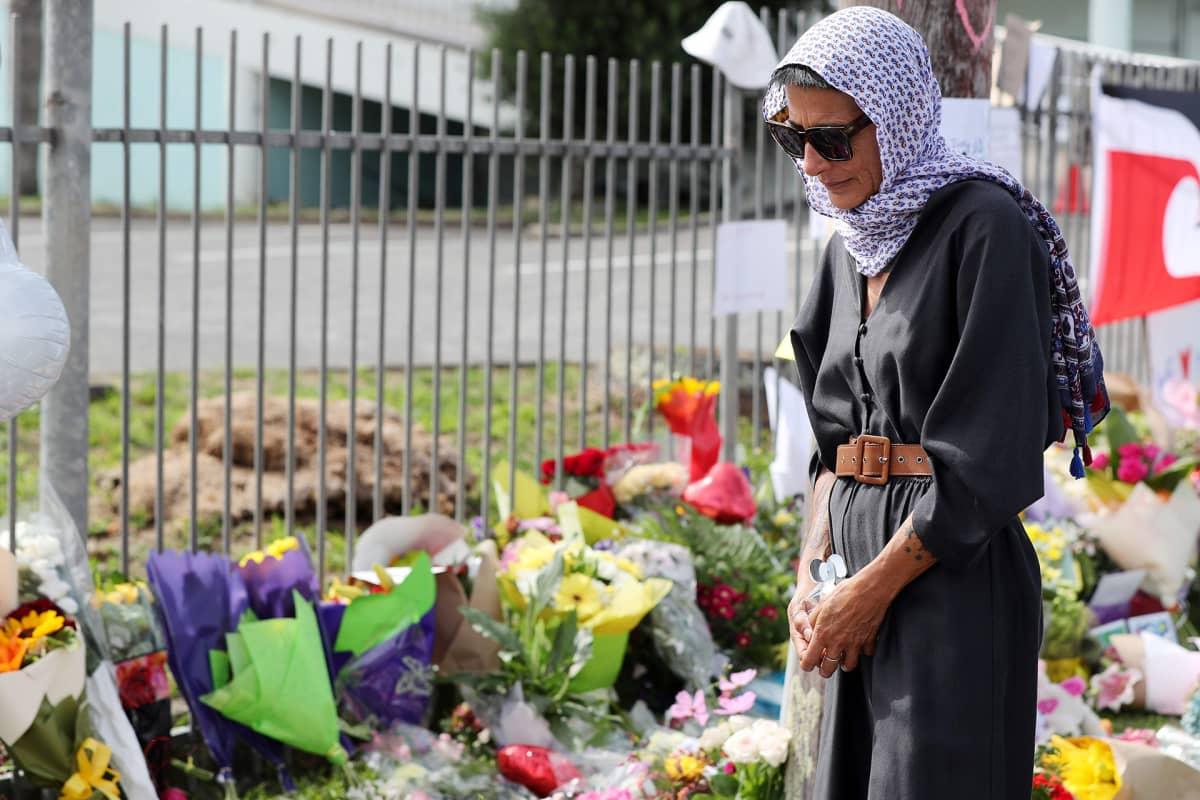 Nainen osoittaa kunnioitustaan iskun uhreille.