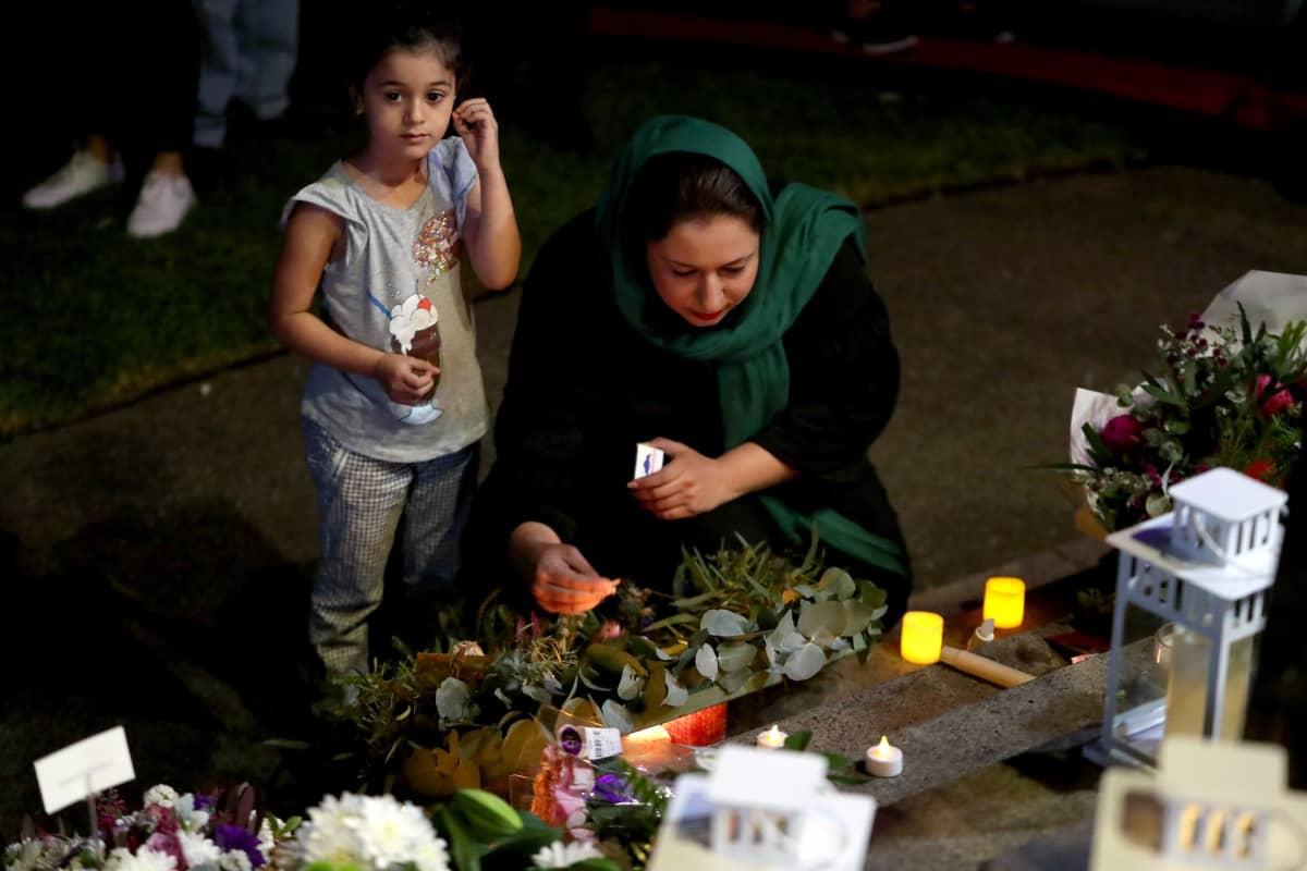 Nainen ja tyttö jättävät kynttilän muistopaikalle.