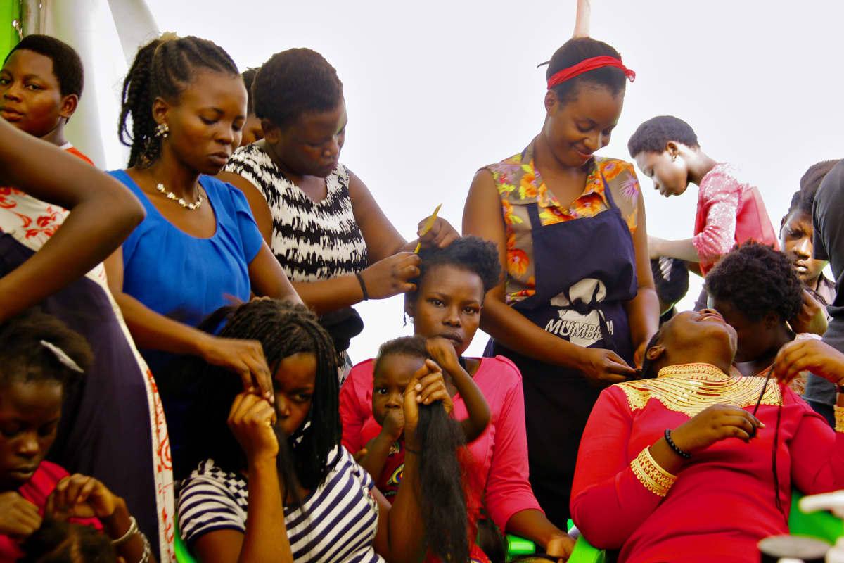 Naisia kampaamassa toisten naisten hiuksia.