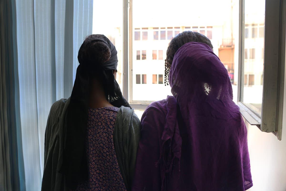 Kaksi tyttöä selin ikkunan edessä.