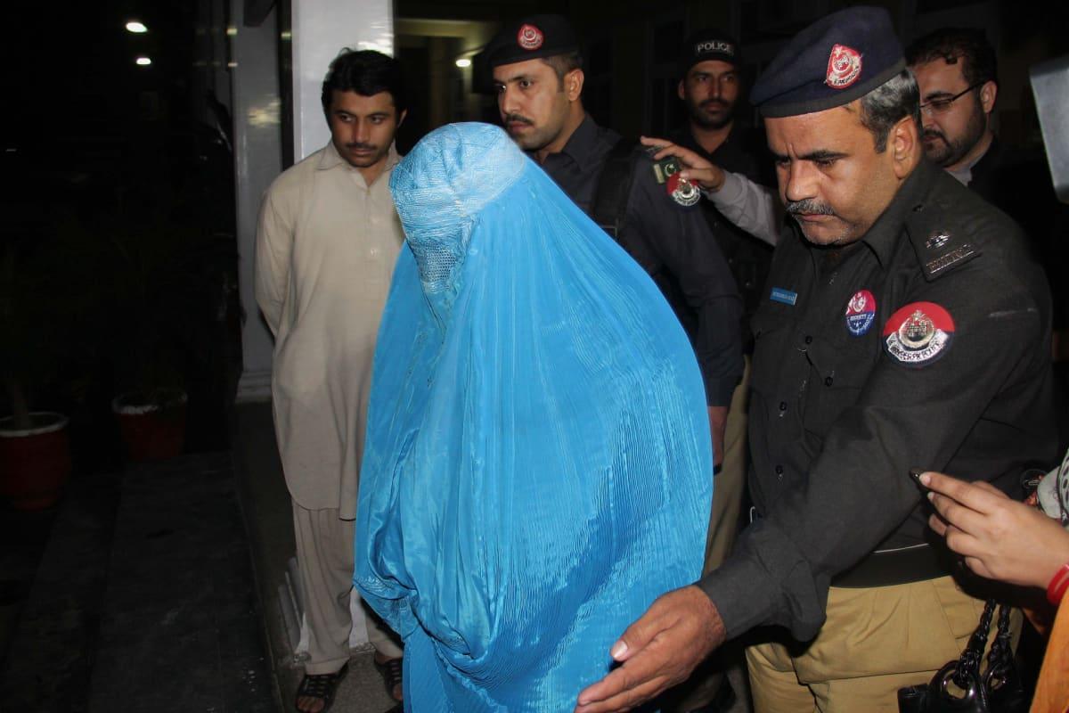 Poliisit saattavat burkhaan pukeutunutta naista.