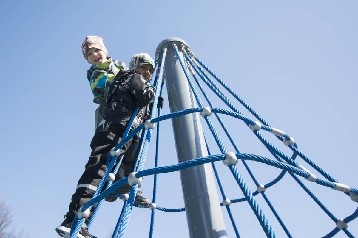 Kasperi Korhonen ja Rahul Fadte kiipeilevät kuopiolaisen leikkipuiston telineessä.