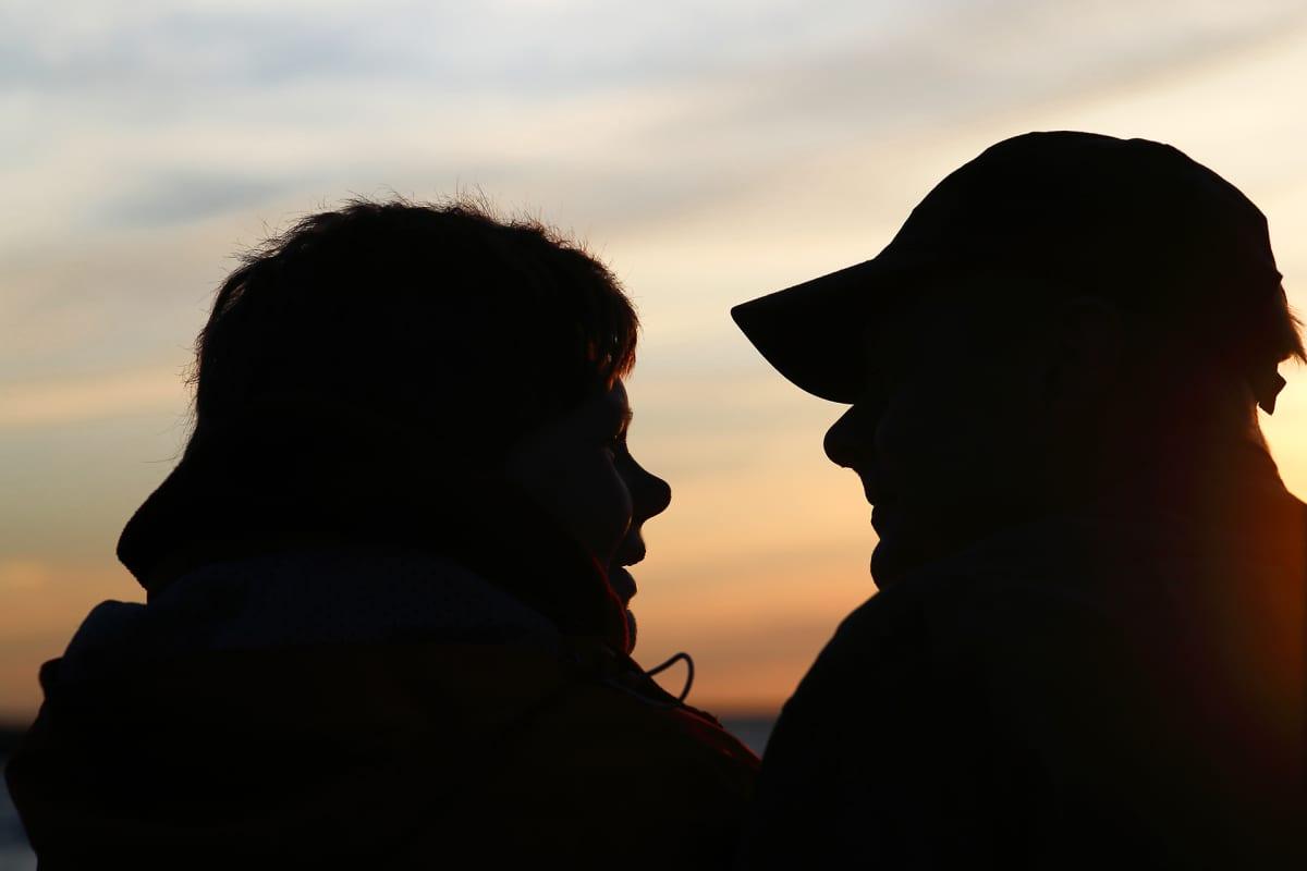 Kaksi henkilöä auringonlaskussa katselevat toisiaan.