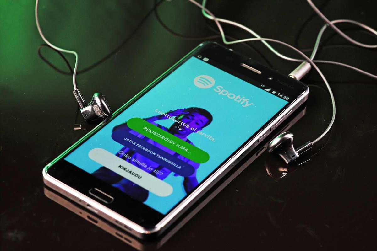 Älykännykkä ja nappikuulokkeet pöydällä. Kännykän näytöllä näkyy Spotifyn sovellus.