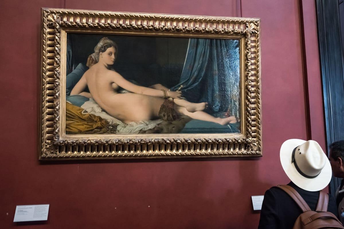 Alastonta naista esittävä maalaus kultakehyksissä. Hattupäinen ihminen taulun edessä.
