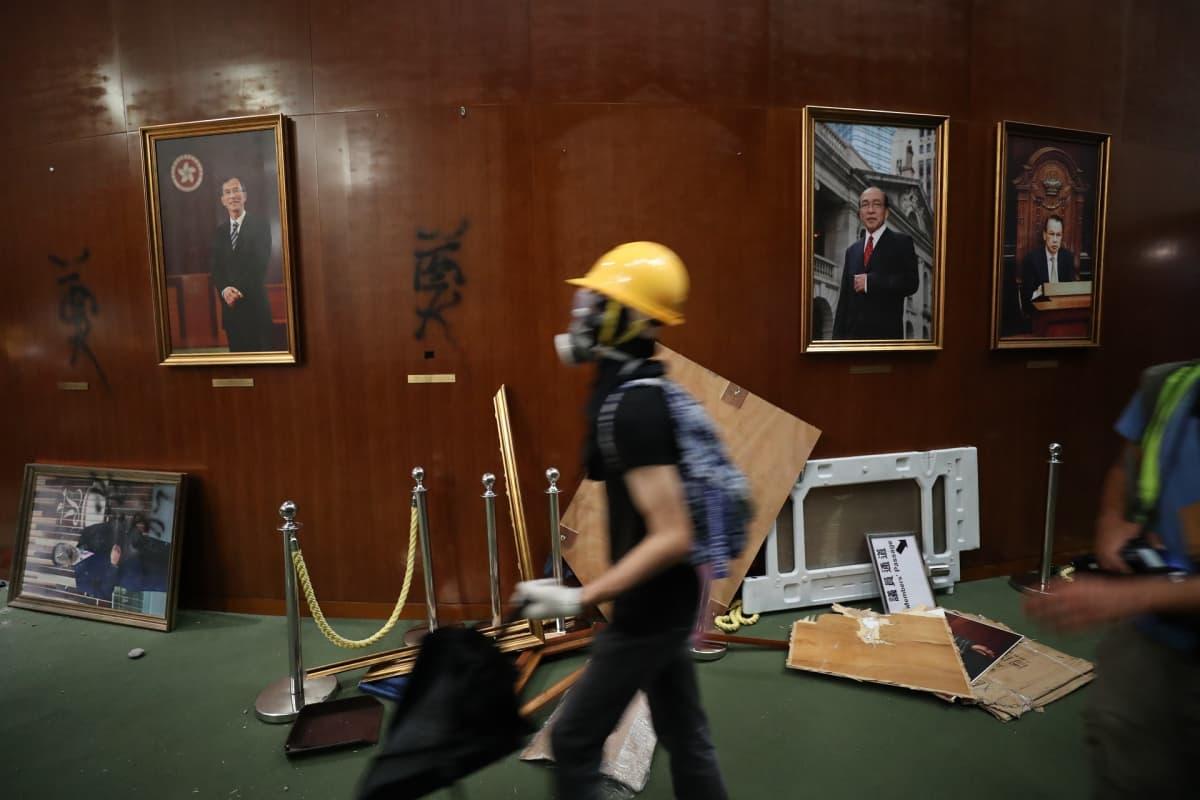 Mielenosoittaja kävelee ohi lattialle pudotettujen taulujen ja seinälle piirrettyjen graffitien.