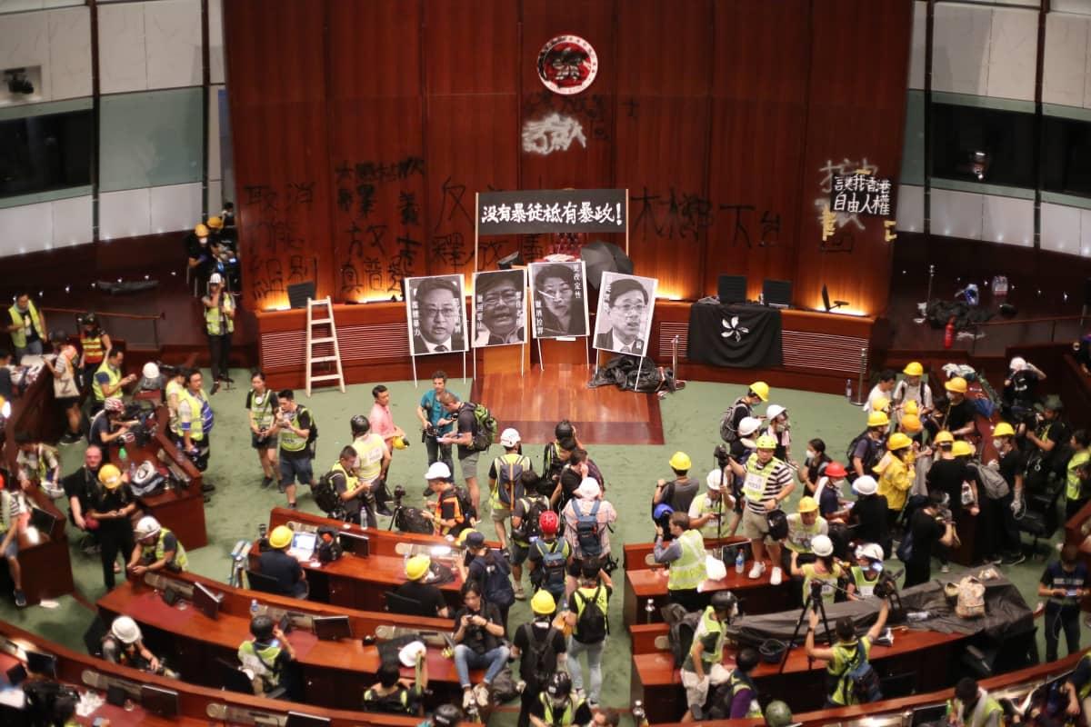 Istuntosali, jossa suuri joukko mielenosoittajia.