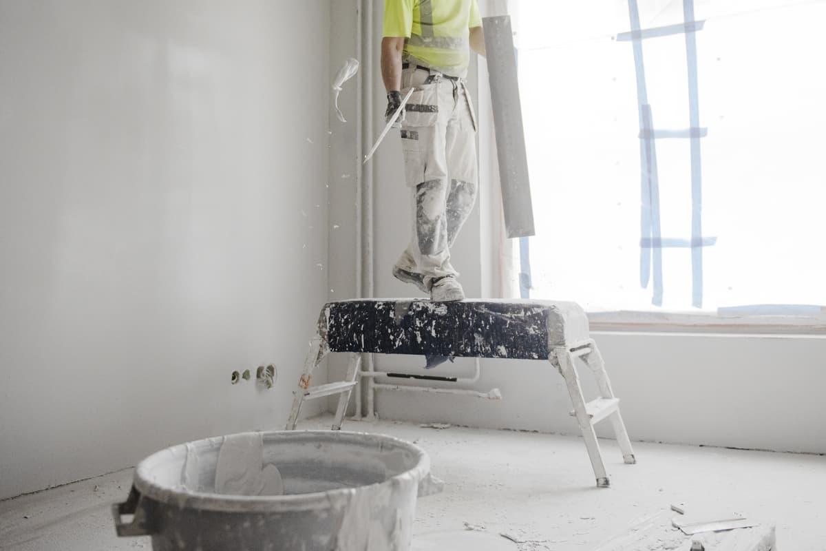 Rakennusmies tekee tasoitustöitä rakennuksella.