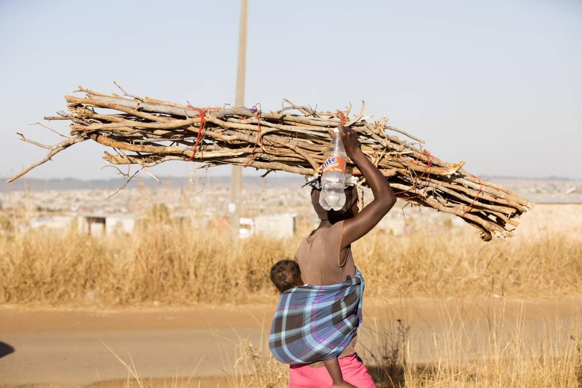 Nainen kantaa polttopuita Hararen kaupungissa Zimbabwessa.