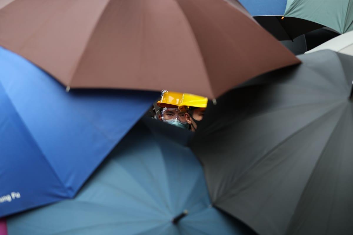 Mielenosoittaja kurkistaa sateenvarjojen keskeltä.