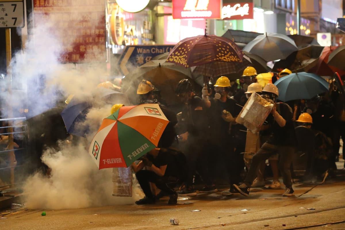 Mielenosoittajia, sateenvarjoja, kyynelkaasua.