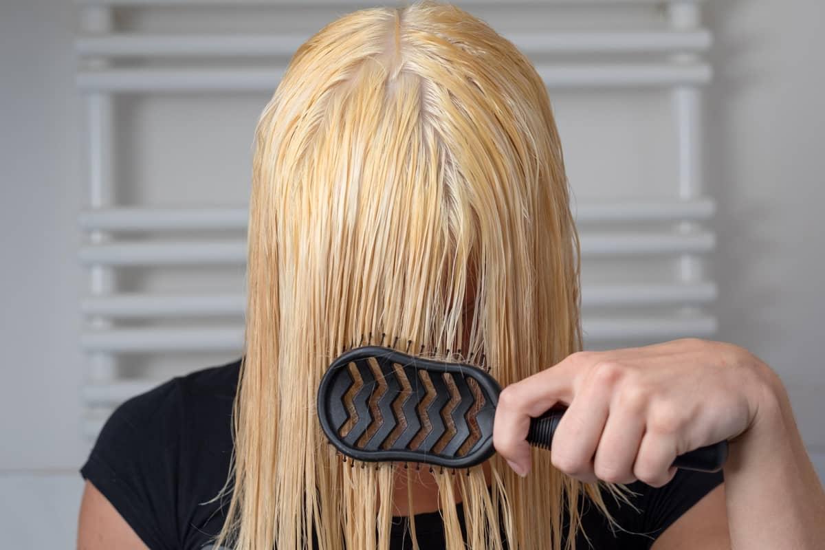 Nainen harjaa hiuksiaan.
