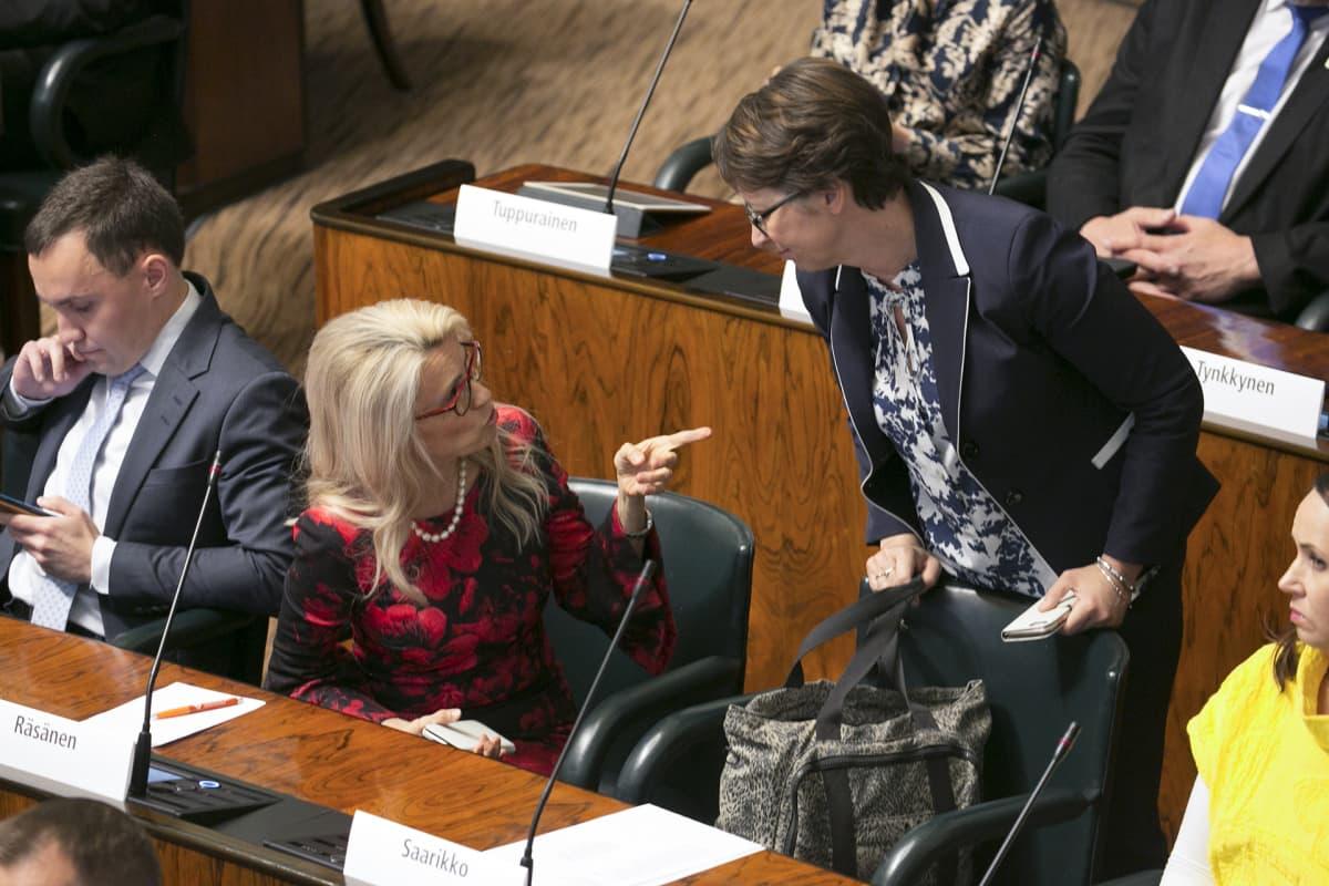 Päivi Räsänen ja Sari Essayah keskustelevat eduskunnan täysistunnossa.