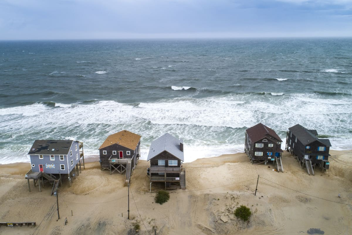 Viisi meren rannalla olevaa rakennusta. Taustalla meri.